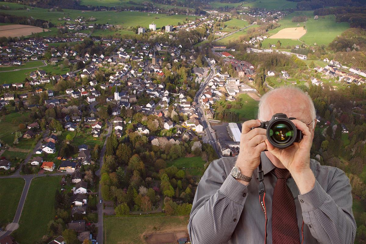 Luftbildaufnahme von Ruppichteroth, Detektiv zeigt Daumen nach oben, Schriftzug: Unserer Detektei ermittelt für Sie in Ruppichteroth !