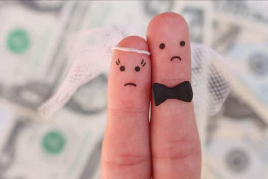 2 Finger die eine Braut und einen Bräutigam darstellen, Im Hintergrund verlorenes Geld durch einen Heiratsschwindler