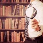 Detektiv recherchiert in einer Bibliothek hat Lupe in der Hand