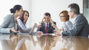 Chef fasst sich an den Kopf wegen den schwierigen Mitarbeitern