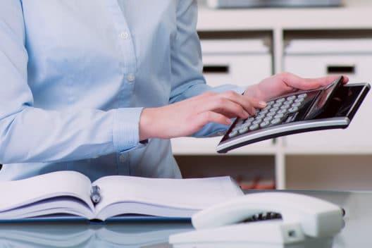 Detektiv rechnet die Kosten für eine Überwachung mit einem Taschenrechner aus.