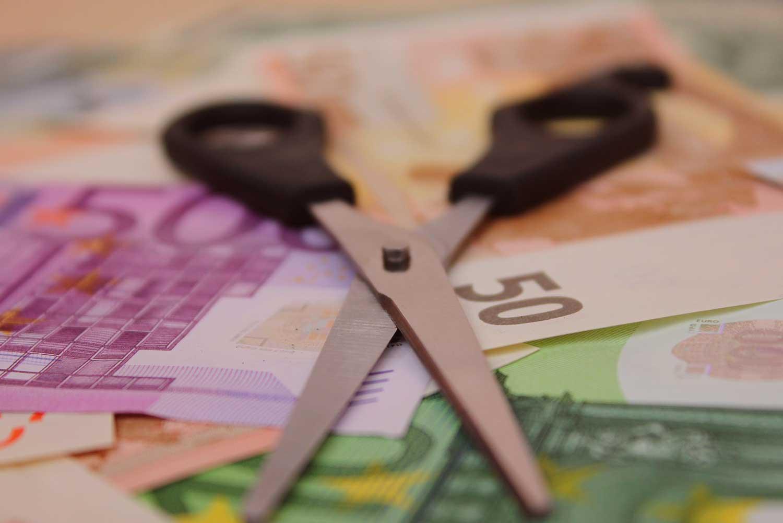Schere auf Stapel Geld. Geld geht durch Korruption verloren