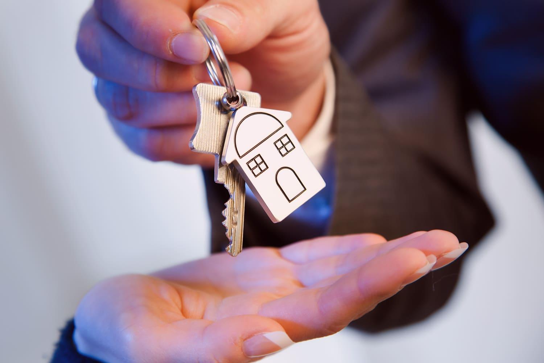 Eine Person übergibt einen Wohnungsschlüssel, Schriftzug: Mietnomaden