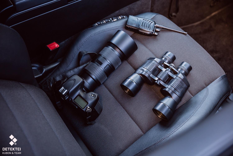privatdetektiv-ausruestung Kamera Fernglas Funkgerät liegen auf Autositz