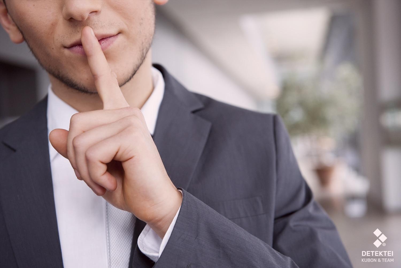 Detektiv hält Zeigefinger vor den Mund