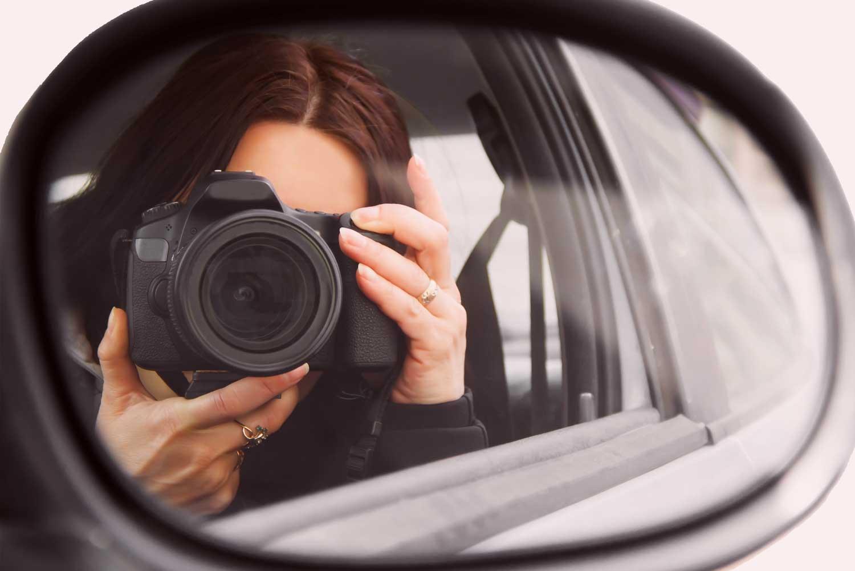 Privatdetektiv in einem Auto mit Kamera vor dem Gesicht durch einen Rückspiegel fotografiert