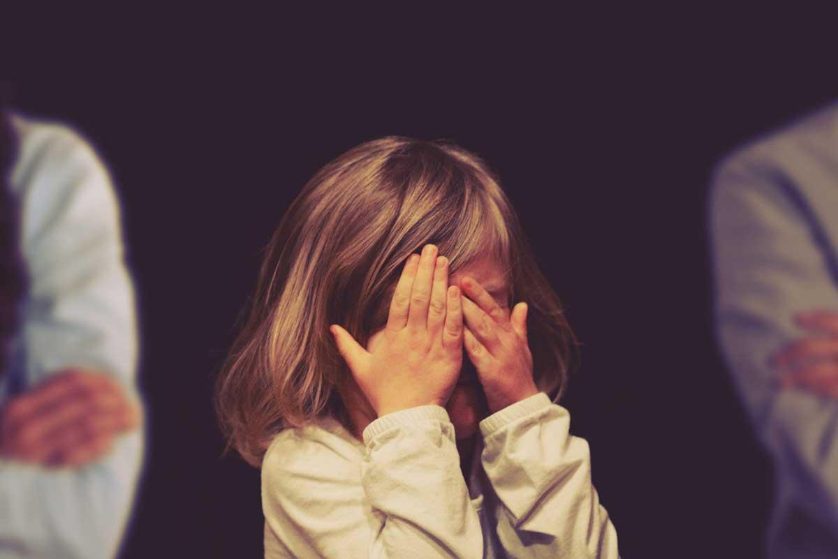 Trauriges Kind hält sich die Hände vor das Gesicht