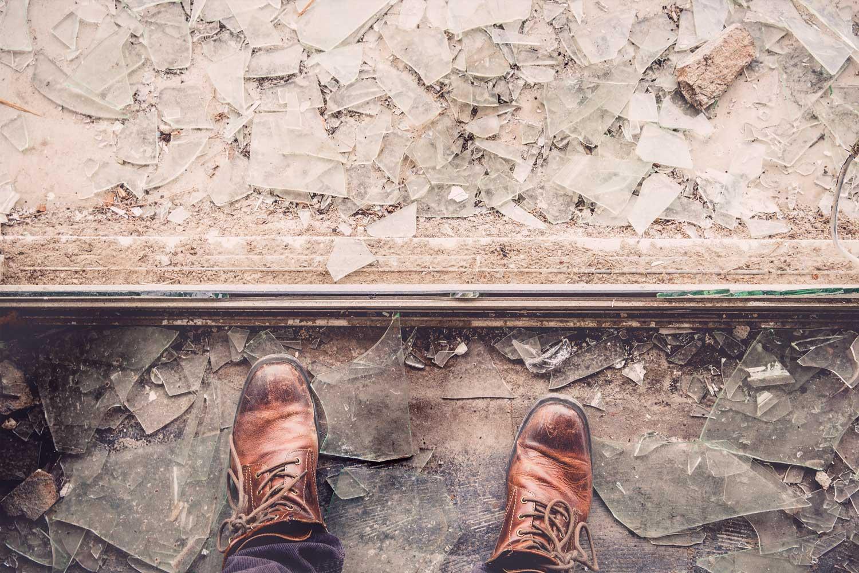 Person steht vor einer zerbrochenen Scheibe. Glas liegt auf dem Boden