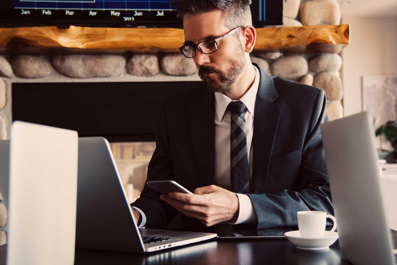 Wirtschaftsdetektiv an Schreibtisch vor einem Laptop